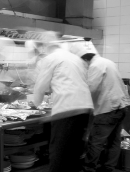 two-blurred-cooks-working-bw.png
